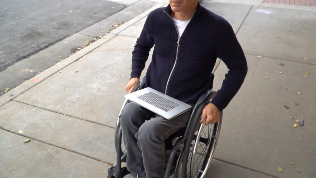 Man in wheelchair on sidewalk with laptop and CatTongue Phat Cat Tablet Grip